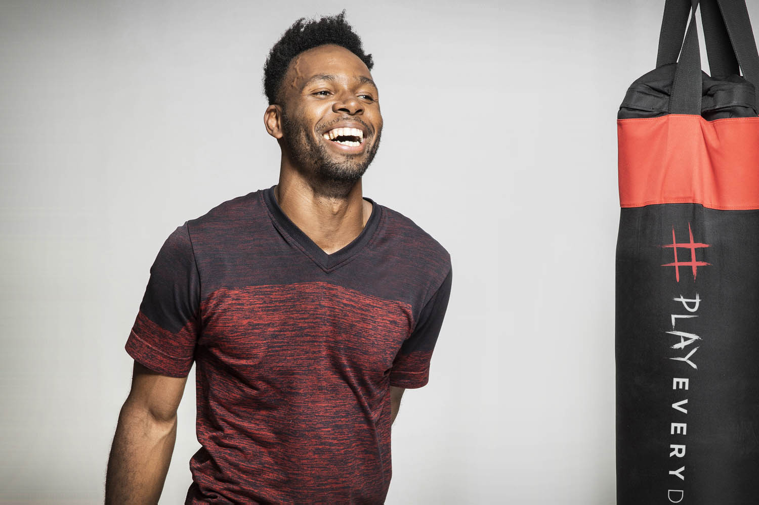 Jason smiles in his workout shirt in front of a punching bag