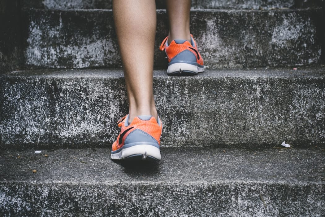 person-in-running-shoes-going-up-stairs